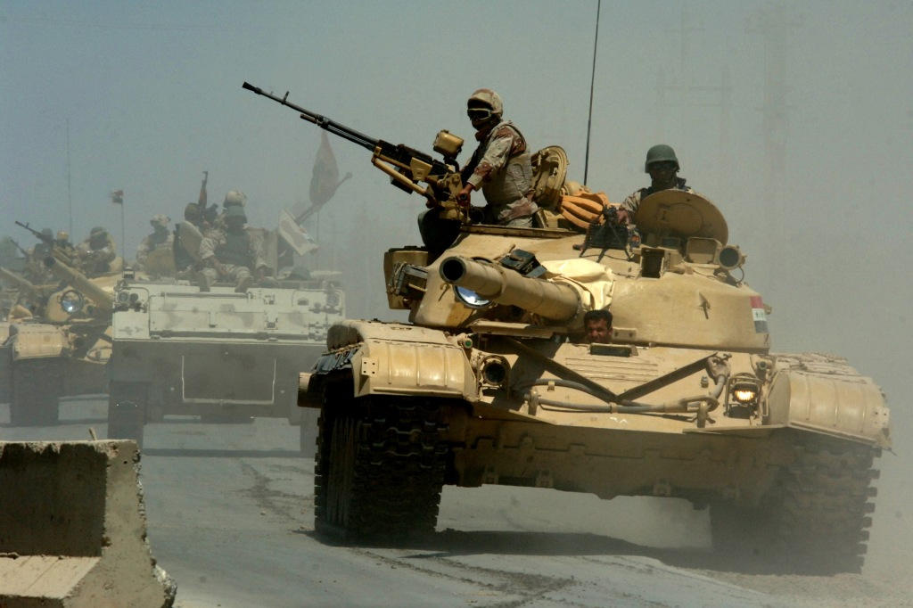 Iraqi Asad Babil tanks and an M113 APC from the Iraqi Army 9th Mechanized Division pass through a highway checkpoint in Mushahada, Iraq.