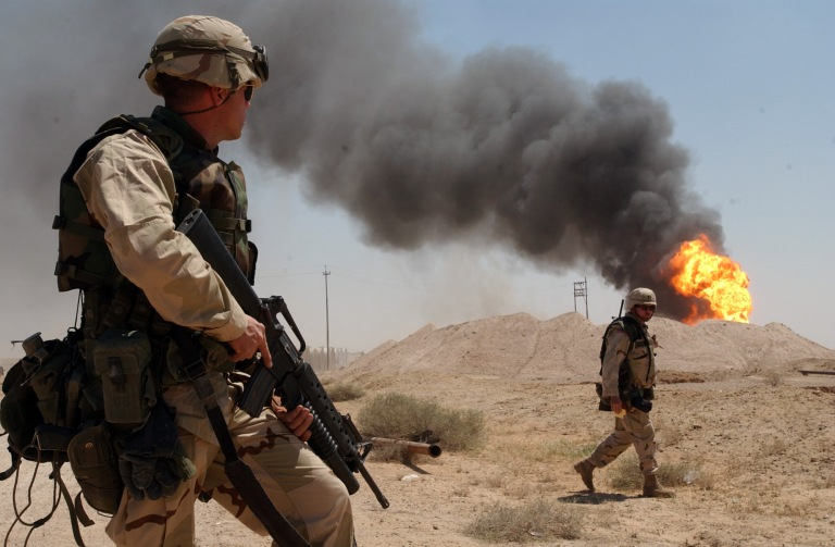 A U.S. soldier stands guard duty near a burning oil well in the Rumaila oil field, 2 April 2003. The 2003 invasion of Iraq has been widely criticized.