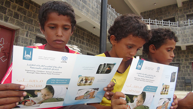 Children in Yemen reading pamphlets about an Islamic Relief program to improve access to education
