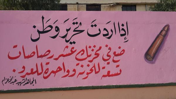 """An IS mural in Tal Afar features a quote from Islamist ideologue Abdullah Azzam: """"If you want to liberate a land, place in your gun ten bullets: nine for the traitors and one for the enemy."""""""