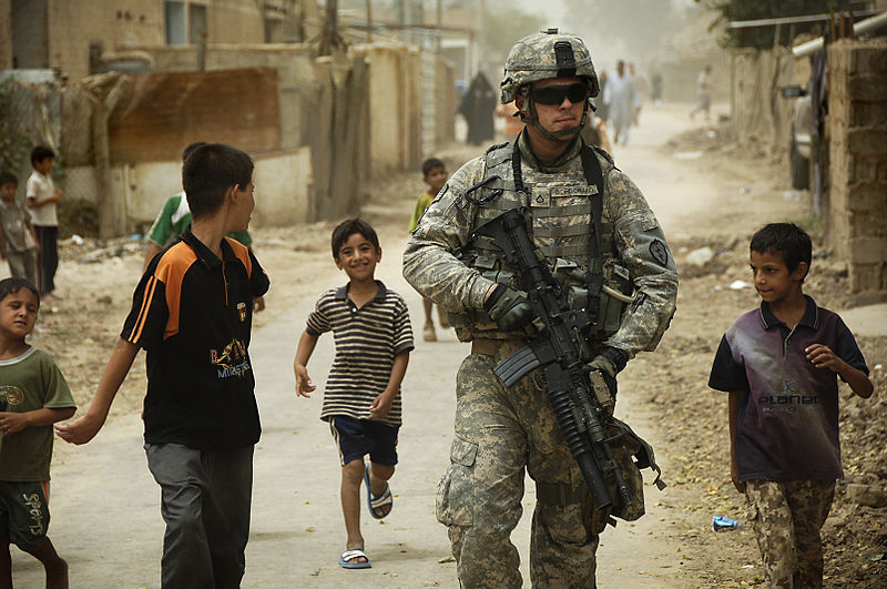 Iraqi children gather around as U.S. Army Pfc. Shane Bordonado patrols the streets of Al Asiriyah, Iraq, August 4, 2008 (Department of Defense)