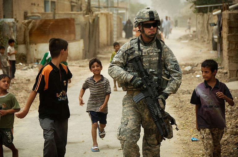 Iraqi children gather around as U.S. Army Pfc. Shane Bordonado patrols the streets of Al Asiriyah, Iraq, August 4, 2008 (Department of Defense)
