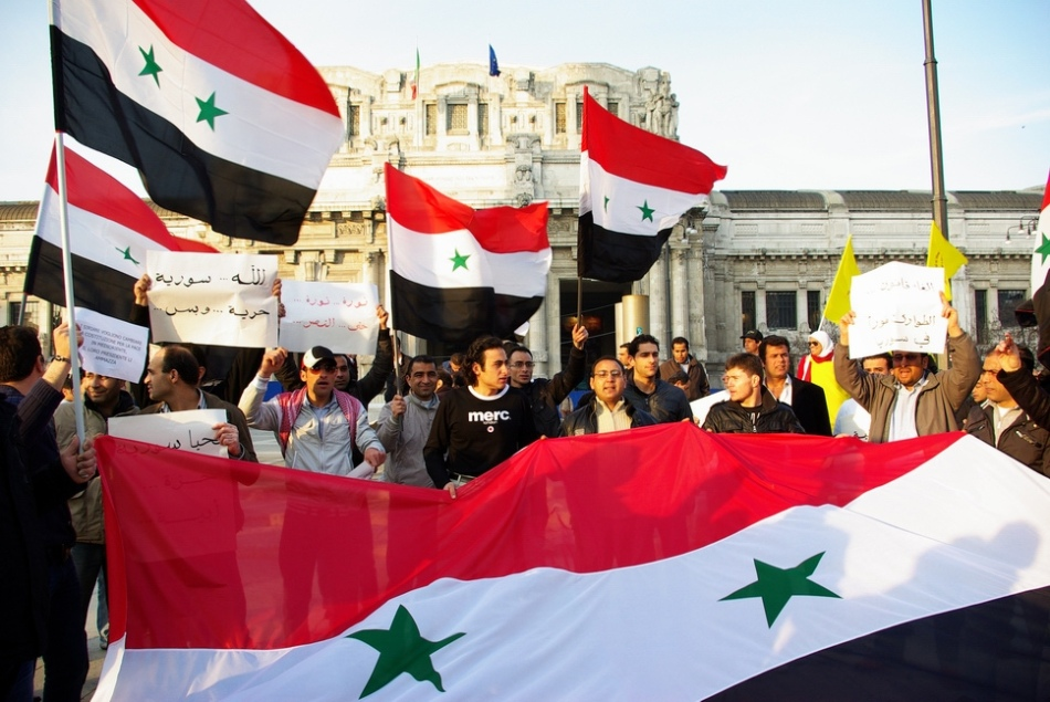 Protestors fly the Syrian national flag at a mass demonstration, March 2011.